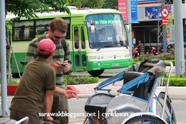 A foreigner believed to be converting the price of a ride on the cyclo as they cyclist persuades him to just hop on.